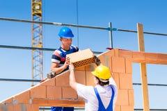 Metselaar of bouwers bij bouwwerf het werken stock afbeelding