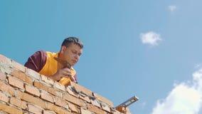 Metselaar die aan een blauwe hemelachtergrond werken stock videobeelden