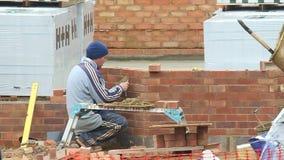 Metselaar die bakstenen in een nieuw bouwstijlhuis richten stock footage