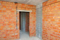 Metselaar die nieuw huis met bakstenen muren, binnenlandse ruimten, bedrading bouwen Stock Foto