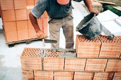 Metselaar die troffel, panmes en mortier voor metselwerk gebruiken, die buiten muren bouwen Stock Foto