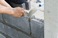 Metselaarhanden die muur met mortier en bakstenen maken royalty-vrije stock fotografie