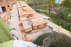 Metselen, Metselwerk De Bakstenen van metselaarsworker installing red en Waterdicht makende de Verbindingen Buitenmuur van het Ba stock afbeelding