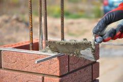 Metselenclose-up Metselaarshand die een stopverfmes houden en een kolom van de baksteenomheining bouwen Stock Foto