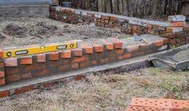 Metselwerk en hulpmiddelen, niveau die, troffel, een huis bouwen stock fotografie