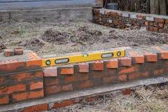 Metselwerk en hulpmiddelen, niveau die, troffel, een huis bouwen stock afbeelding