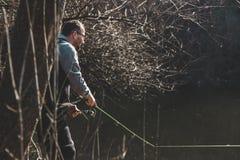 Metspö och händer av fiskaren över sjövattnet fotografering för bildbyråer