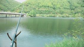 Metspöet står på ställningen som väntar på fisken att nicka stock video