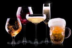 Metta con differenti bevande su fondo nero Fotografie Stock