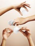 Metta con le mani di una donna su un fondo beige Fotografia Stock Libera da Diritti