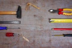 Metta degli attrezzi per bricolage isolati su fondo di legno, con area di lavoro per il vostro testo immagine stock libera da diritti