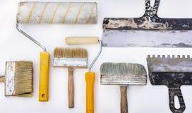 Metta degli strumenti d'annata della pittura della mano su un fondo bianco fotografia stock