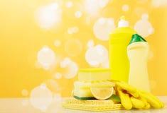 Metta degli strumenti per pulire la cucina Detersivo per i piatti, spugna su fondo giallo luminoso immagini stock