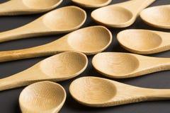 Metta dei cucchiai di legno - fondo nero immagine stock