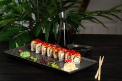 metta dei rotoli di sushi su una banda nera su un fondo di legno nero con le foglie verdi di una pianta da appartamento fotografia stock libera da diritti