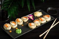 metta dei rotoli di sushi su una banda nera su un fondo di legno nero con le foglie verdi di una pianta da appartamento immagine stock