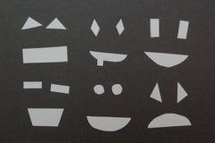 Metta dei sorrisi di carta su un fondo grigio illustrazione di stock