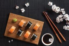 Metta dei sushi e dei rotoli di maki con il ramo dei fiori bianchi sulla tavola di pietra fotografie stock