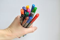Metta dell'arcobaleno ha colorato le penne che tengono in mano della donna, su fondo bianco fotografie stock