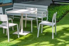 Metta della decorazione bianca di legno delle sedie e della tavola in giardino fotografia stock