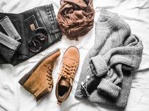 Metta delle attrezzature l'autunno, i vestiti dell'inverno - i jeans, il pullover grigio di grande misura, stivali marroni delle  immagini stock