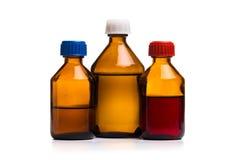 Metta delle bottiglie di vetro mediche su un fondo bianco fotografie stock libere da diritti