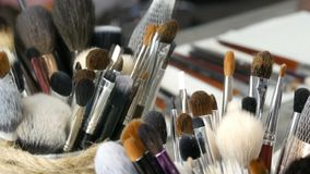 Metta delle spazzole professionali per trucco sulla tavola nello spogliatoio Industria della moda Manifestazione di alta moda die stock footage