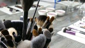 Metta delle spazzole professionali per trucco sulla tavola nello spogliatoio Industria della moda Manifestazione di alta moda die video d archivio