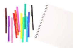 Metta di dodici indicatori della penna a feltro nei colori differenti e di uno sketchbook in bianco con uno spazio per testo Isol immagine stock