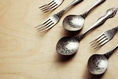 Metta di retro forchette e cucchiai incisi Concetto dinamico immagini stock libere da diritti