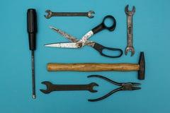 Metta di vecchi strumenti arrugginiti su un fondo blu fotografia stock