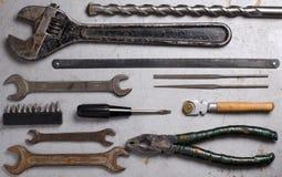 Metta di vecchi strumenti della mano su fondo grigio fotografie stock libere da diritti
