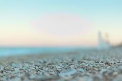 Metta a fuoco il dettaglio sulle pietre della luce di mattina sulla spiaggia vicino alla riva fotografia stock