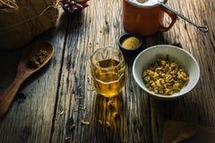 Metta a fuoco il tè del crisantemo del punto ed il crisantemo secco su una vecchia tavola di legno Immagine Stock