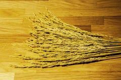 Metta a fuoco la punta asciutta del riso sul pavimento di legno nel fondo Fotografia Stock Libera da Diritti