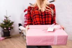 Metta a fuoco su un giftbox in mani della donna nella priorità alta Bella bionda in un cappello di Santa, in una camicia rossa in Immagine Stock Libera da Diritti