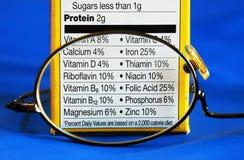 Metta a fuoco sui fatti di nutrizione da una scatola di alimento Immagine Stock
