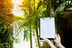 Metta a fuoco sul documento che la ragazza compila il modulo di domanda di visto per l'Australia contro il contesto delle palme e Fotografia Stock Libera da Diritti