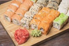 Metta i rotoli di sushi con il caviale, il salmone, il sesamo, lo zenzero ed il wasabi Fotografie Stock