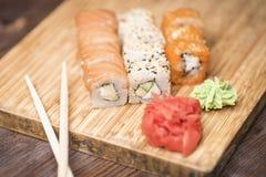 Metta i rotoli di sushi con il salmone, il sesamo, il caviale rosso, l'avocado, lo zenzero, il wasabi ed i bastoni per i sushi Fotografia Stock