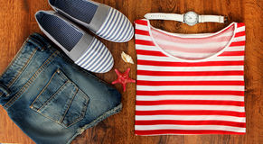 Metta i vestiti per andare al mare: shorts dei jeans, una camicia a strisce e scarpe da tennis, orologi, coperture, vista superio Fotografia Stock