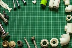 Metta l'impianto idraulico e gli strumenti su un fondo verde Fotografia Stock Libera da Diritti