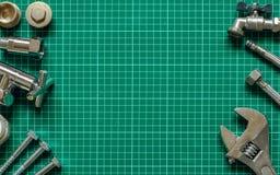 Metta l'impianto idraulico e gli strumenti su un fondo verde Immagini Stock
