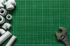 Metta l'impianto idraulico e gli strumenti su un fondo verde Fotografia Stock