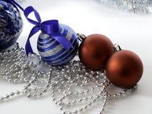 Metta la bagattella di Natale con il nastro su bianco immagini stock
