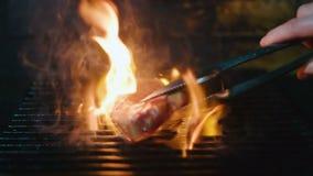 Metta la carne sulla griglia Colpo del movimento lento di cottura della bistecca sulla griglia stock footage