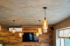 Metta la retro lampada di edison sul fondo di legno della parete del sottotetto fotografia stock