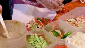 Metta la verdura sulla tortiglia per fare gli involucri di verdure video d archivio