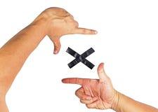 Metta le mani il fuoco sul segno nero di x Sui precedenti bianchi fotografie stock libere da diritti