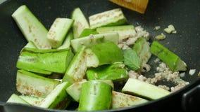 Metta le melanzane del pezzo affettate verde nella pentola stock footage